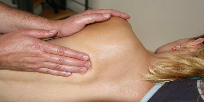 Ein Mann massiert einer Frau den Rücken