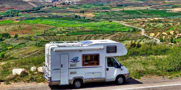 Ein Wohnmobil Parkt vor einer Hügellandschaft auf der Straße