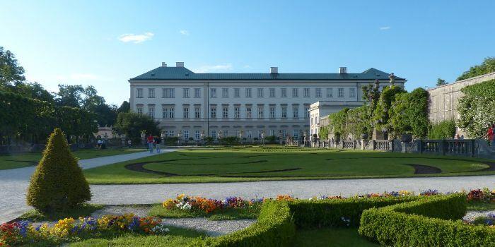 Das Schloss Mirabell in Salzburg mit einem grünen Garten davor