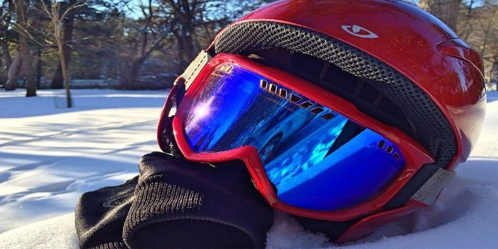 Ein Skihelm, eine Skibrille und Handschuhe liegen im Schnee
