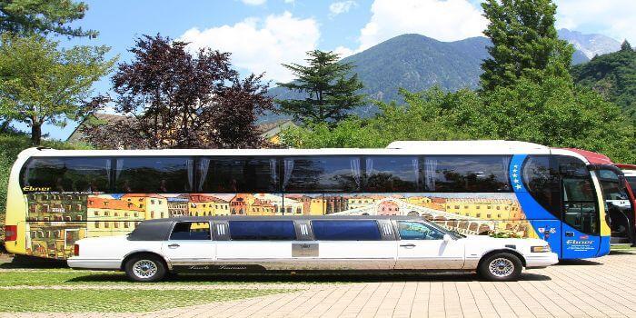 Eine Stretchlimousinen steht vor einem bunten Reisebus
