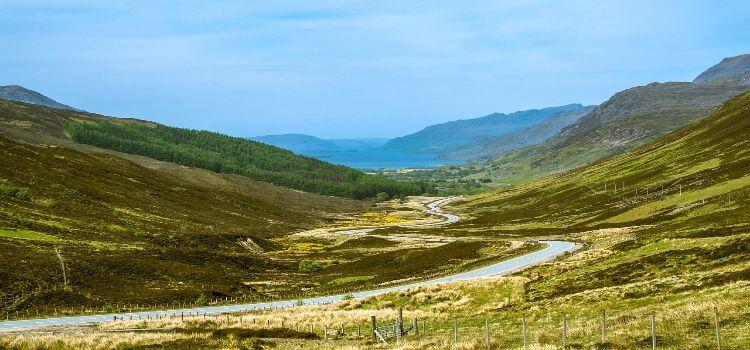 Eine Straße schlängelt sich durch die Landschaft in Schottland