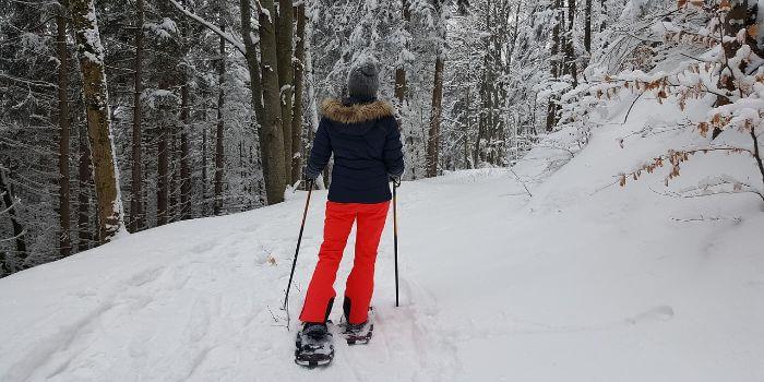 Eine Frau wandert mit Schneeschuhen entlang eines Weges im Tiefschnee