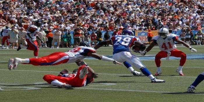 Zwei Football Spieler stürzen sich auf den gegner um Ihn zu stoppen