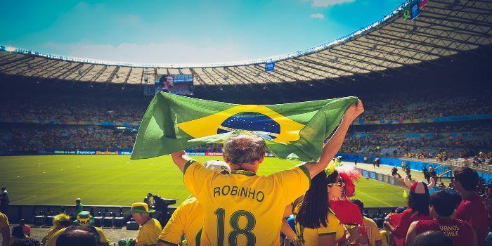 Ein brasilianischer Fußball Fan hält eine Flagge in die Höhe