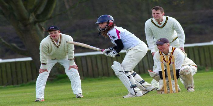 Vier Cricket Spieler stehen konzentriert auf dem Rasen