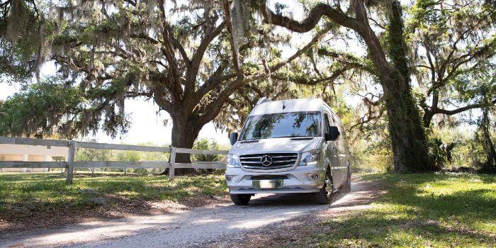 Ein Van fährt auf einer Straße wo links und rechts Bäume stehen