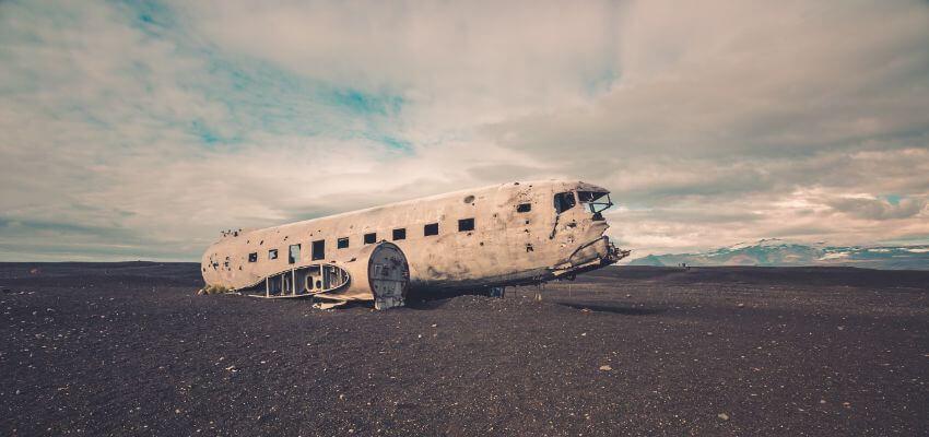 Ein Flugzeugwrack auf einem schwarzen Vulkan Boden.