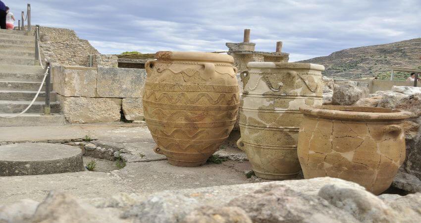 Auf dem Bild sieht man große antike Töpfe die auf dem historischen Gelände von Knossos stehen.