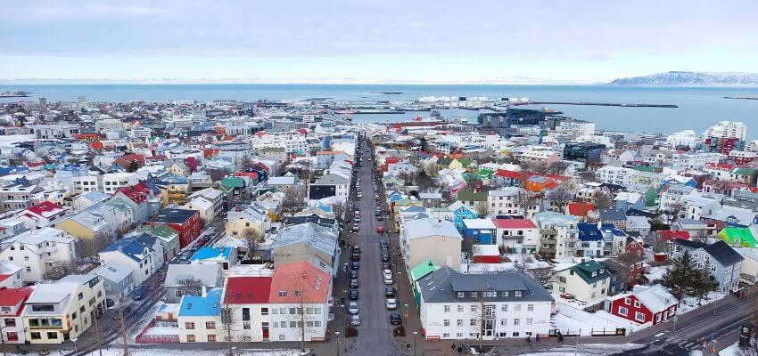 Bild von oben auf Reykjavik. Viele weiße kleine Häuser mit bunten Dächern sind zu sehen.