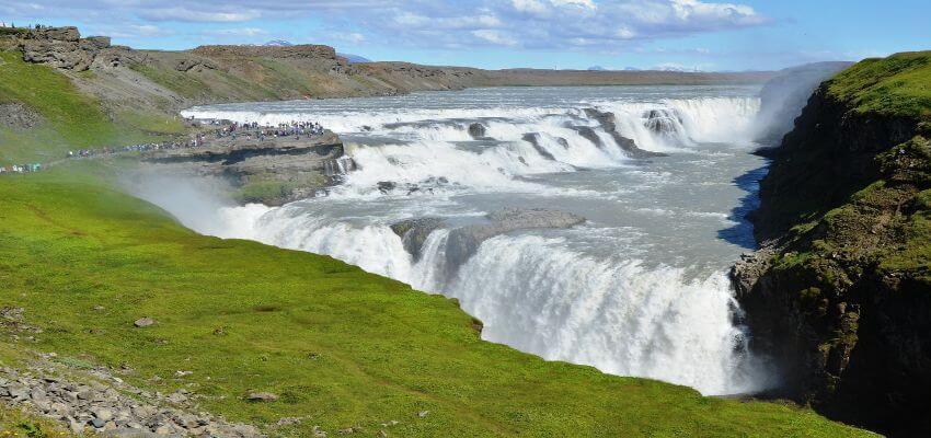 Ein mächtiger und breiter Wasserfall umgeben von einer grünen Moos bedeckten Umgebung.