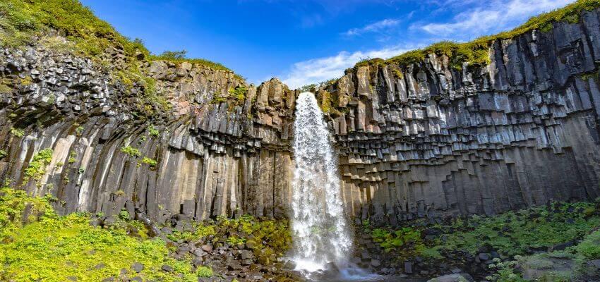 Schmaler Wasserfall umgeben von einer Steinmauer.