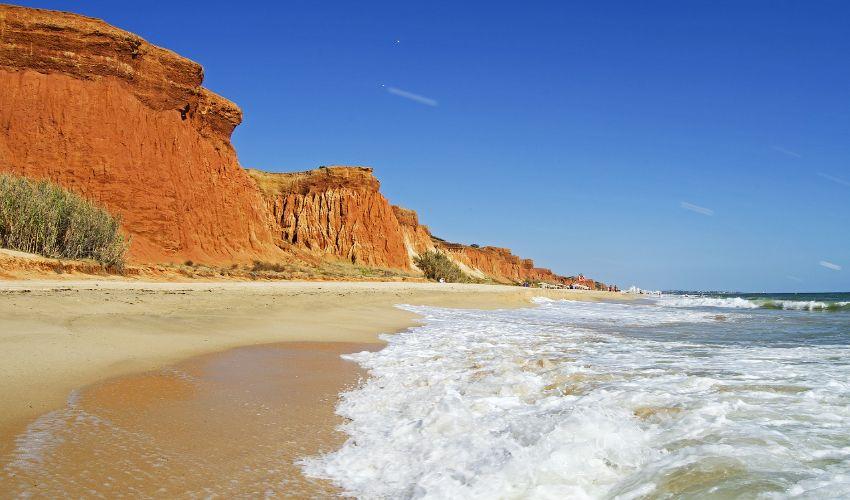 Sandstrand mit Klippen aus rotem Sandstein im Hintergrund.
