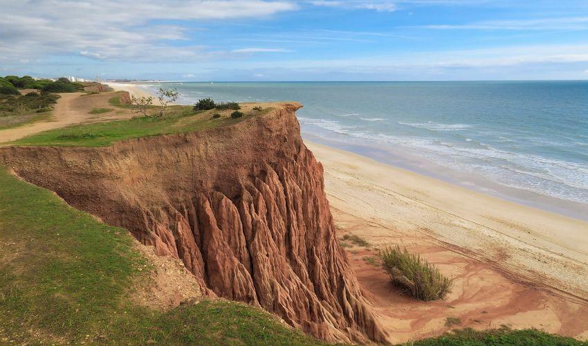 Sandstrand mit roter Klippenwand im Hintergrund.