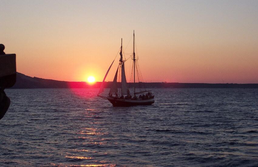Ein Segelboot mit dem Sonnenuntergang im Hintergrund.