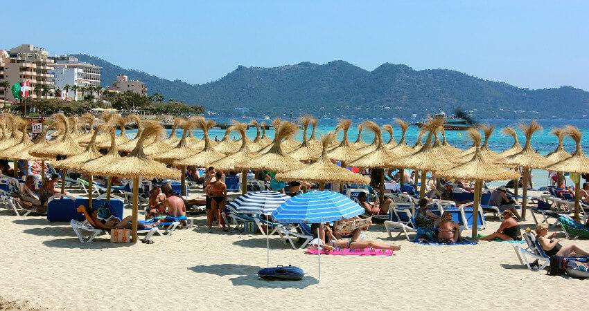 Viele Touristen am Sandstrand unter Stroh Sonnenschirme.