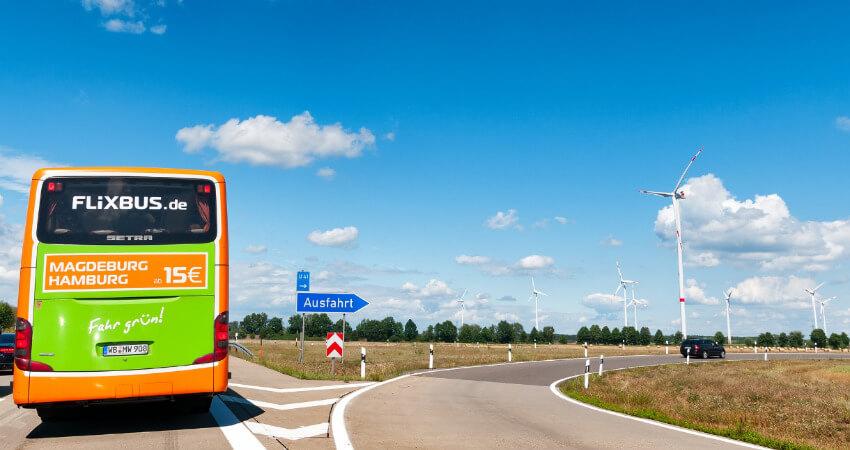 Ein grüner Flixbus fährt auf die Autobahn auf.