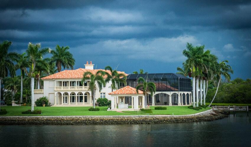 Eine große Villa mit Gewitterwolken im Hintergrund.