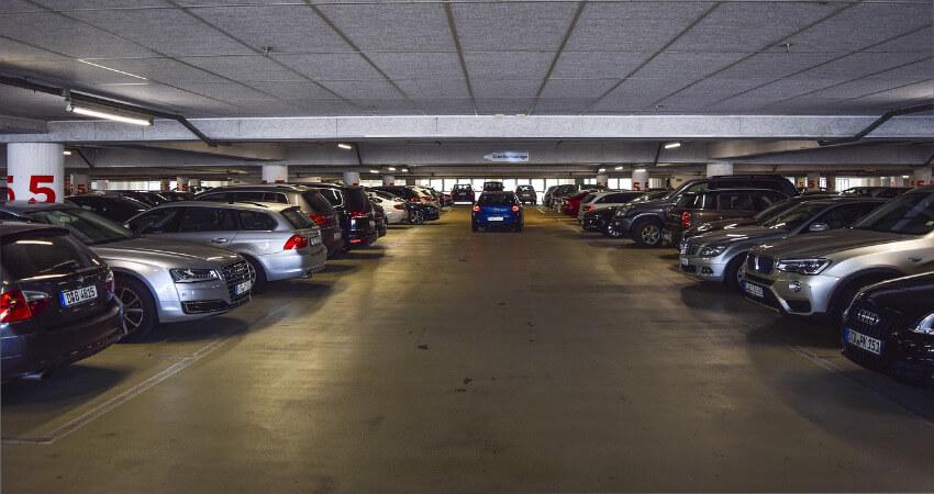 Ein volles Parkdeck, wobei ein blaues Auto Richtung Ausfahrt fährt.