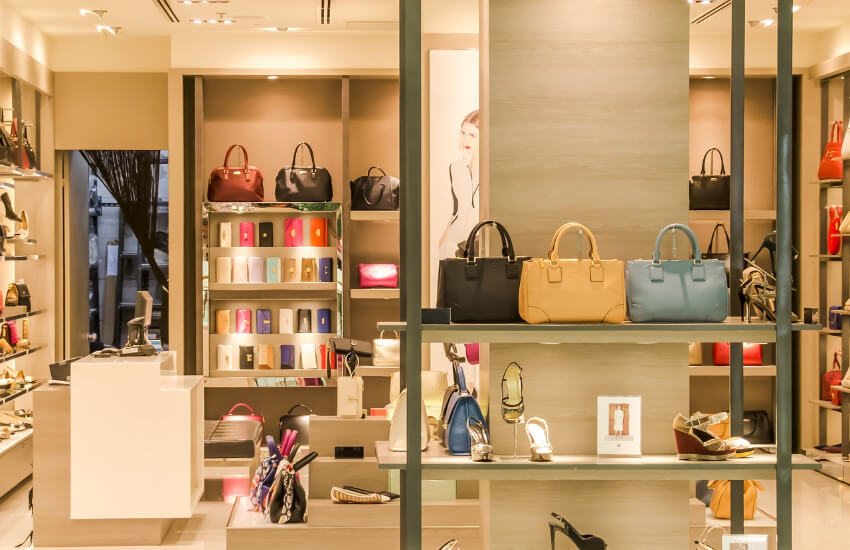 Eine hell beleuchtete Boutique wo Schuhe und Handtaschen ausgestellt sind.