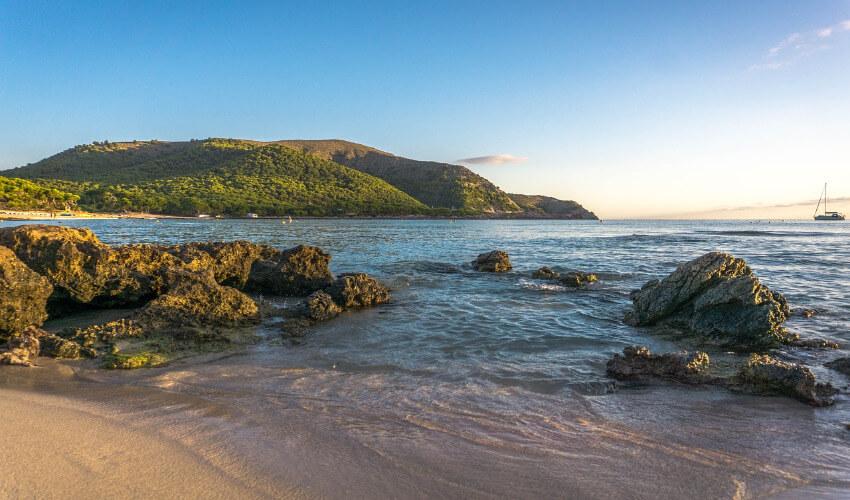 Ein einsamer Strand mit großen Felsen im seichten Wasser.