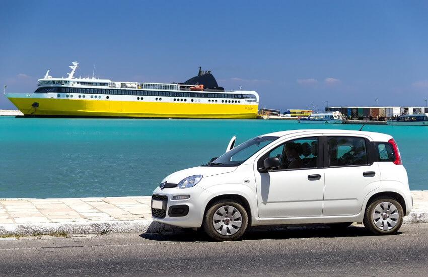 Ein Auto parkt am Straßenrand und im Hintergrund das Meer mit einem Kreuzfahrtschiff.