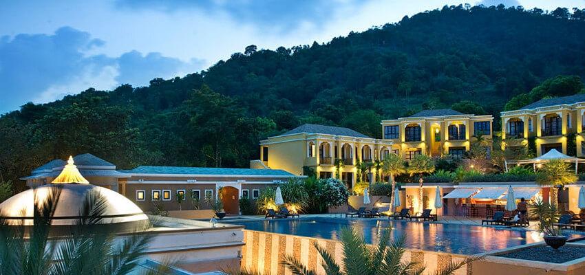 Ein Spa Hotel in der Abenddämmerung, wobei die Fassade des Hotels beleuchtet ist. Vor dem Hotel befindet sich ein Pool.