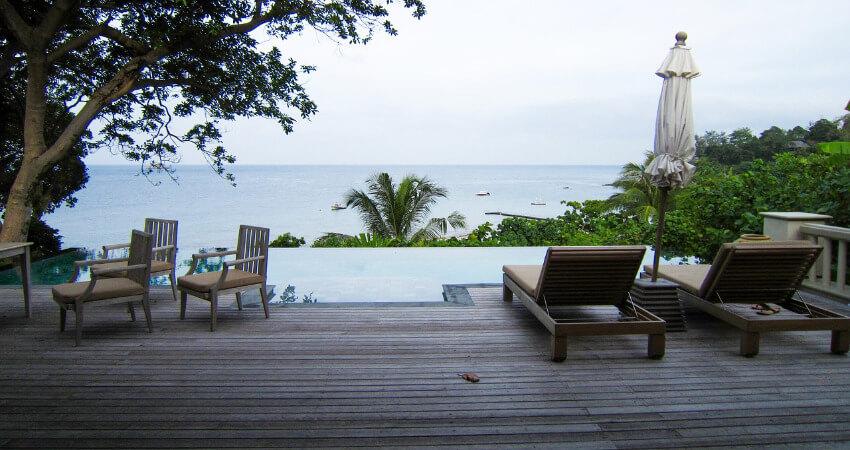 Eine Terrasse mit Liegestühlen und Sesseln mit Blick aufs Meer.