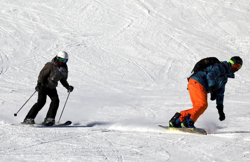 Eine Frau auf Skier und ein Mann auf den Snowboard flitzen eine Skipiste hinunter.