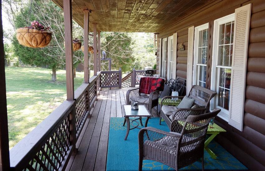 Eine Terrasse eines Ferienhauses mit Rattanstühlen.