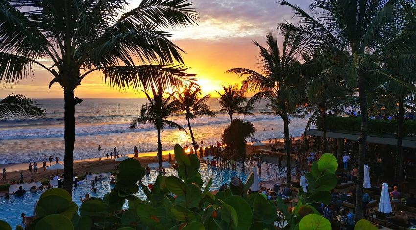 Strand auf Bali mit Palmen und Restaurant bei Sonnenuntergang.