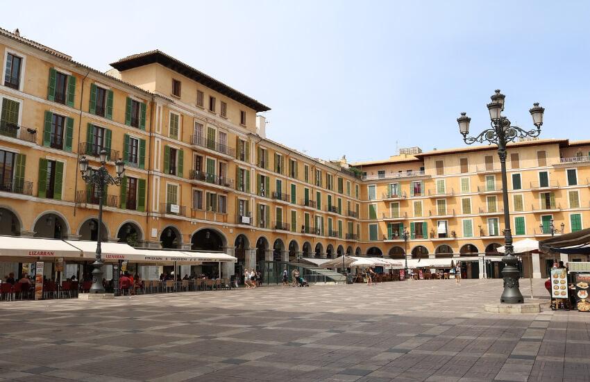 Großer rechteckiger Platz mit vielen Geschäften, Cafés und Restaurants.
