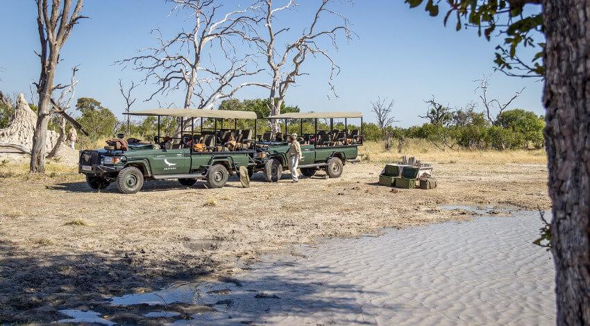 Zwei dunkelgrüne Geländewagen seitlich offen mit einem Stoffdach als Sonnenschutz.