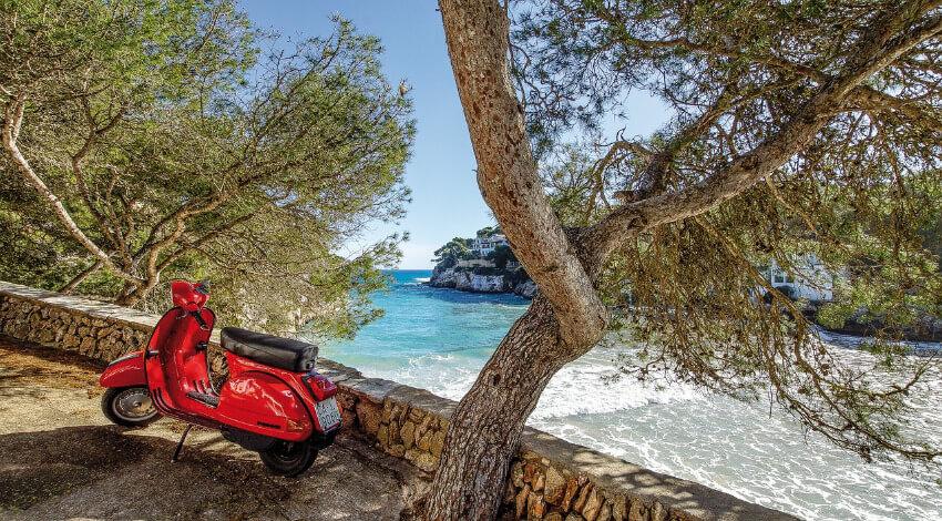 Ein roter Roller abgestellt am Straßenrand mit Blick auf die Bucht Cala Santanyí.