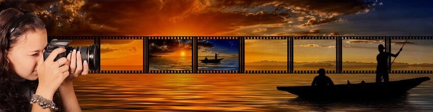 Eine Fotografin macht ein Foto vom Meer und einem kleinem Fischerb0ot in der Abenddämmerung.