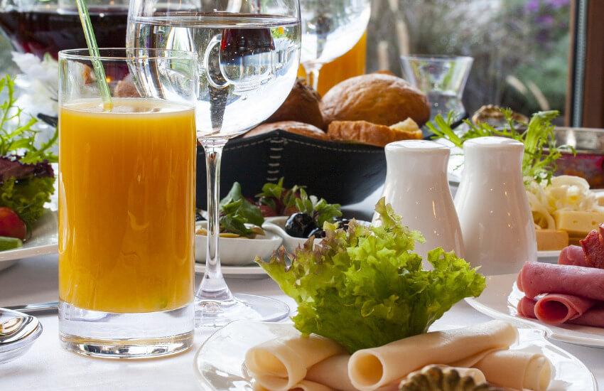 Ein Frühstückstisch mit Orangensaft, Wasser, Putenschinken, Salat und weiteren gesunden Lebensmitteln.