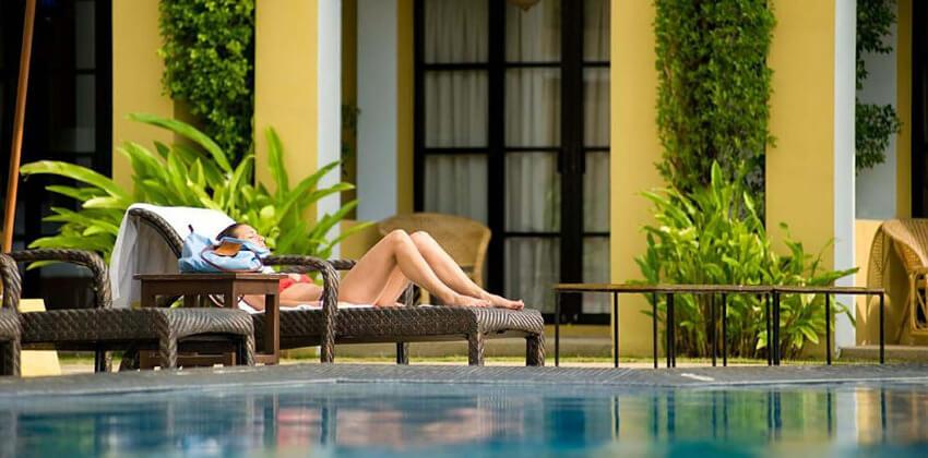 Eine Frau liegt in einem Liegestuhl am Pool.