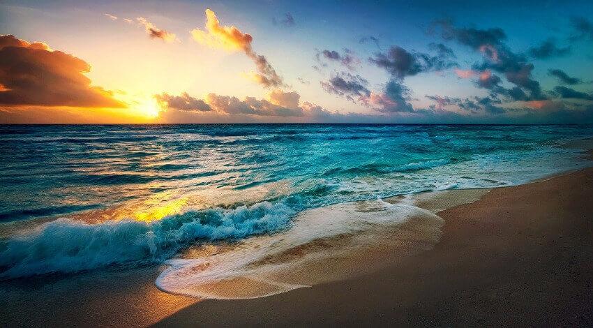 Ein Sonnenaufgang über blauem Meer und Sandstrand.