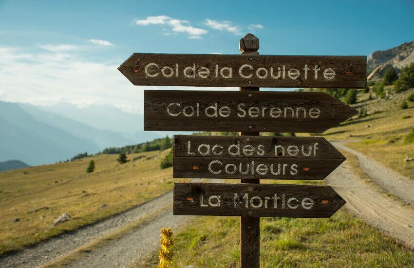 Ein Wegweiser aus Holz steht am Berg und zeigt vier Wanderrouten an.