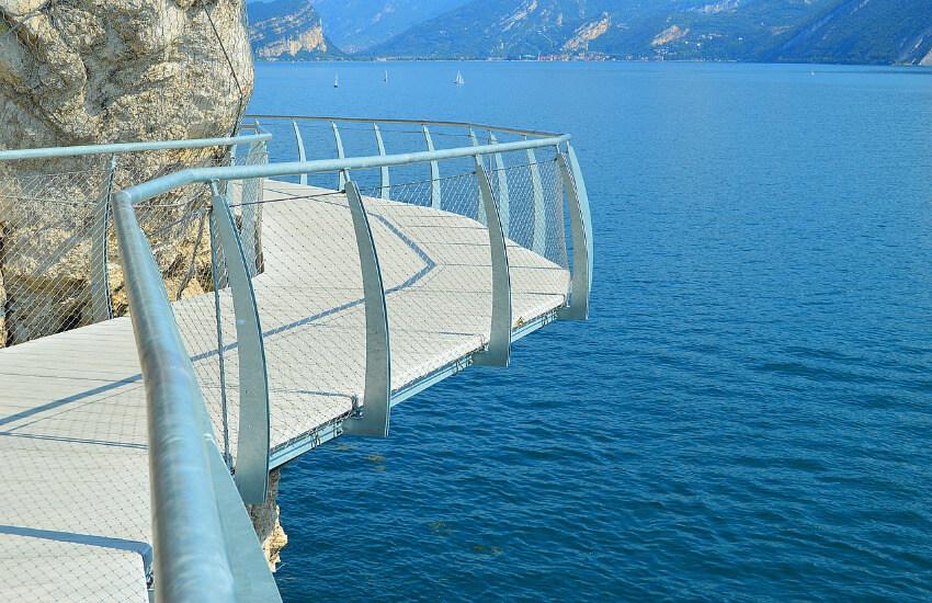 Ein Steg, der an einer Klippe entlang geht. Direkt darunter der Gardasee.