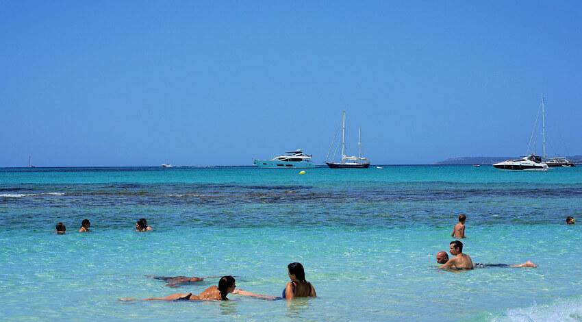 Ein paar Touristen liegen im flach abfallenden Meer und genießen die Sonne.