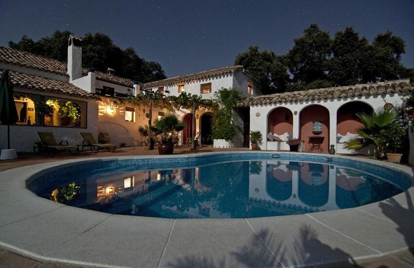 Der Hinterhof einer Villa mit einem steinumrandeten Swimmingpool.