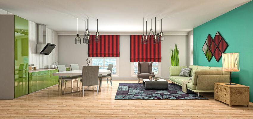 Ein Wohnraum mit Küchenzeile mit grüner Front, einem weißen Esstisch und gegenüber eine grüne Couch.